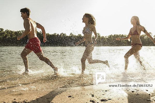 Drei Freunde beim Laufen am Fluss