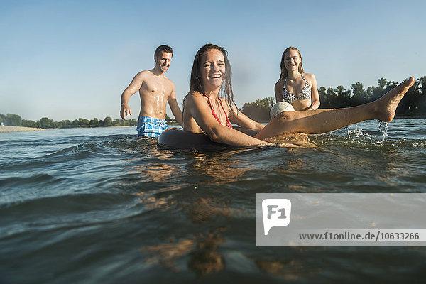 Glückliche Freunde mit Schlauch und Ball im Wasser