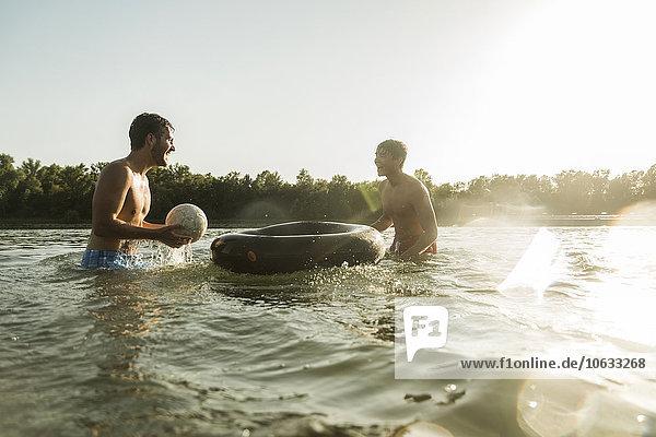 Zwei Freunde mit Schlauch und Ball im Wasser