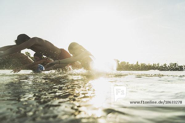 Glückliche Freunde beim Planschen im Wasser Glückliche Freunde beim Planschen im Wasser