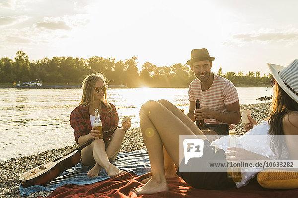 Freunde beim Sonnenuntergang am Flussufer entspannen