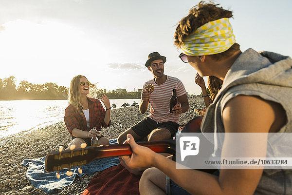 Freunde mit Gitarre entspannen am Flussufer bei Sonnenuntergang