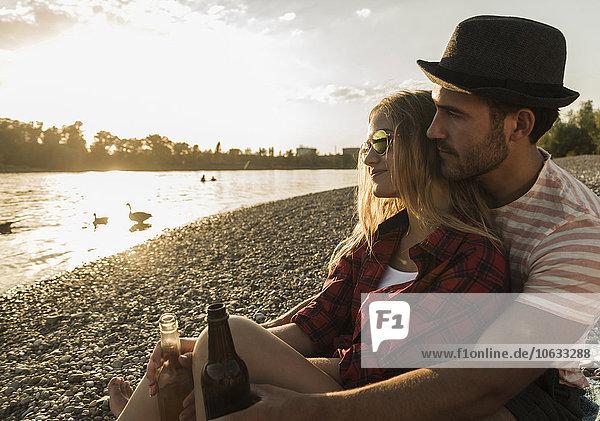 Junges Paar entspannt sich bei Sonnenuntergang am Flussufer