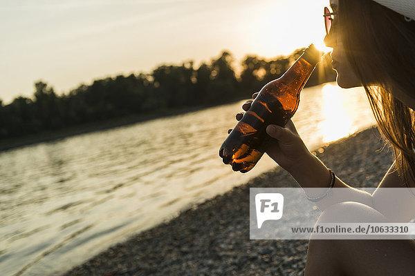 Junge Frau beim Biertrinken am Flussufer bei Sonnenuntergang