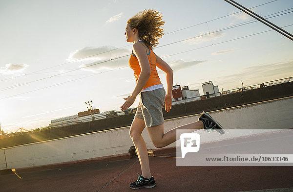 Teenage girl running on a bridge