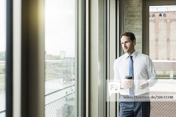 Portrait eines Geschäftsmannes mit Kaffee zum Mitnehmen und Smartphone mit Blick durchs Fenster