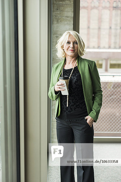 Portrait der blonden Geschäftsfrau mit Kaffee zum Mitnehmen und Smartphone