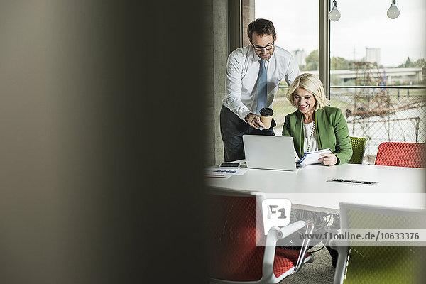 Zwei Geschäftsleute betrachten Laptop in einem Büro