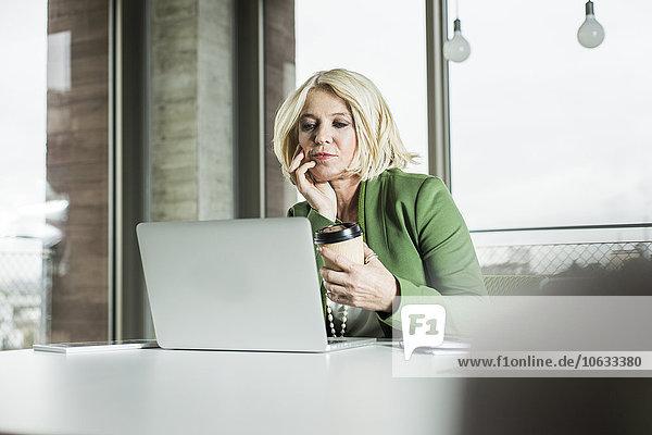 Porträt einer denkenden Geschäftsfrau mit Kaffee zum Anschauen ihres Laptops im Büro