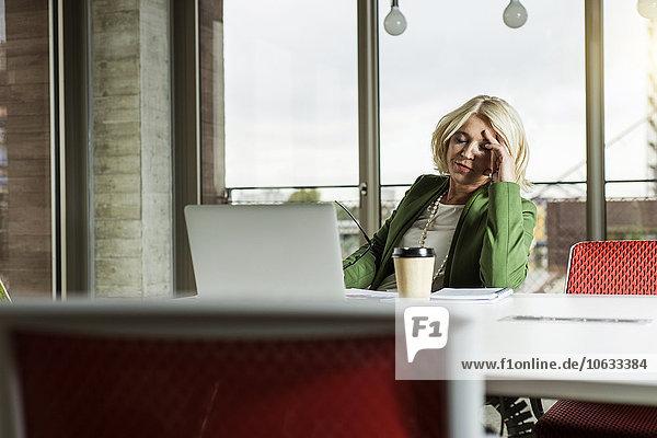 Portrait Geschäftsfrau mit geschlossenen Augen am Schreibtisch im Büro