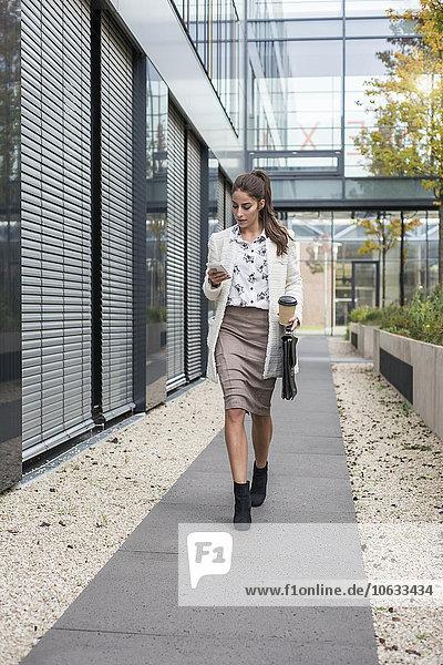 Junge Geschäftsfrau im Freien zu Fuß und mit Blick auf Handy
