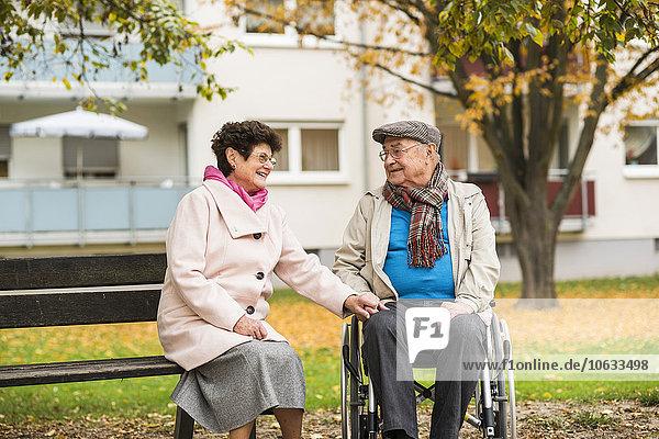 Seniorin auf der Bank neben dem Ehemann im Rollstuhl sitzend