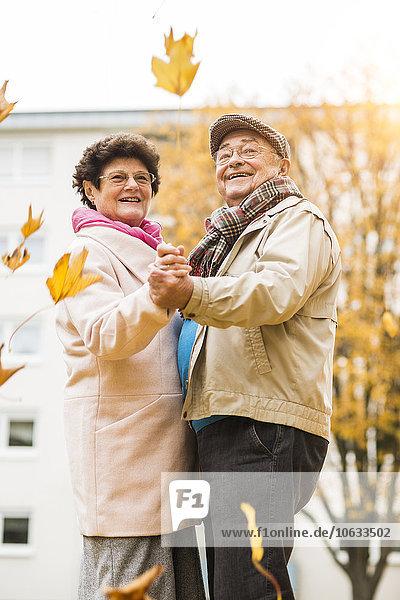 Fröhliches Seniorenpaar tanzt im Herbst im Freien
