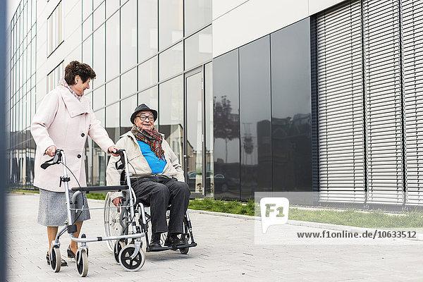 Seniorin mit Rollator und Senior im Rollstuhl auf dem Bürgersteig
