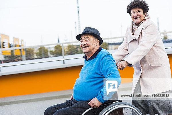 Seniorin schiebt Ehemann im Rollstuhl