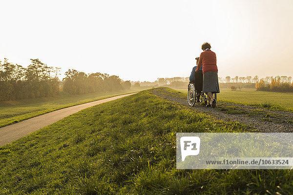 Seniorin schiebt Ehemann im Rollstuhl in der Natur