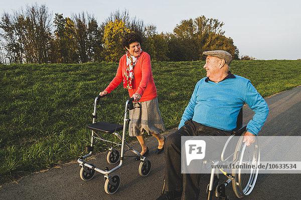Lächelndes Seniorenpaar mit Rollstuhl und Rollator auf einem Weg