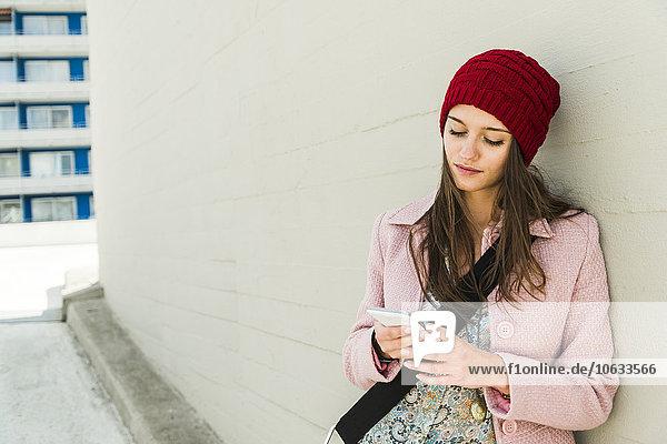 Junge Frau lehnt sich an die Betonwand und schaut auf das Handy.