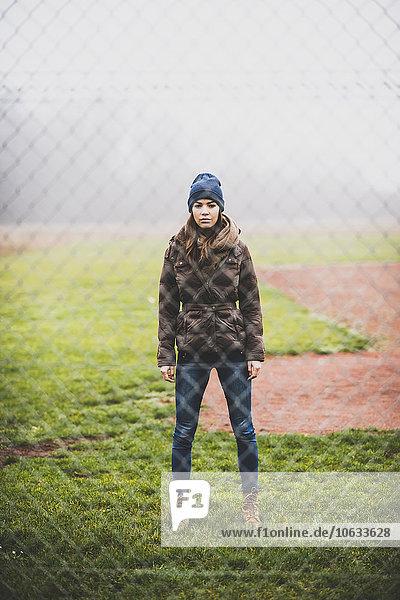 Junge Frau steht auf einer Wiese hinter einem Drahtgeflecht