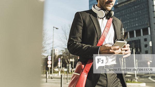 Deutschland  Frankfurt  Junge Geschäftsleute  die mit einer Tasse Kaffee durch die Stadt spazieren gehen  mit dem Handy