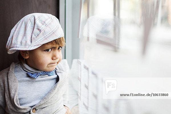 Porträt des wütenden kleinen Jungen mit Mütze durchs Fenster schauend Porträt des wütenden kleinen Jungen mit Mütze durchs Fenster schauend