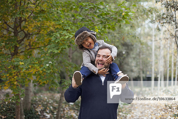 Ein lachender kleiner Junge  der auf den Schultern seines Vaters sitzt.