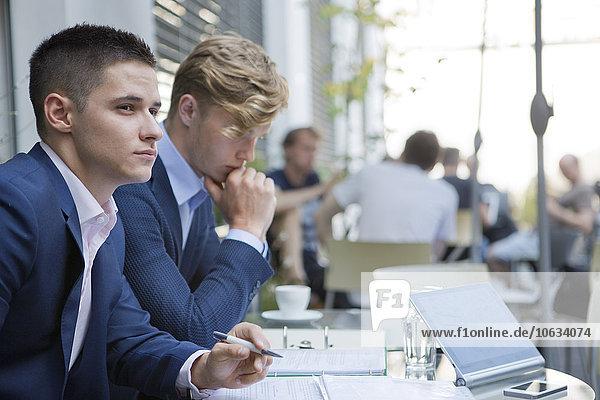 Zwei Geschäftsleute mit Dokumenten am Tisch im Freien