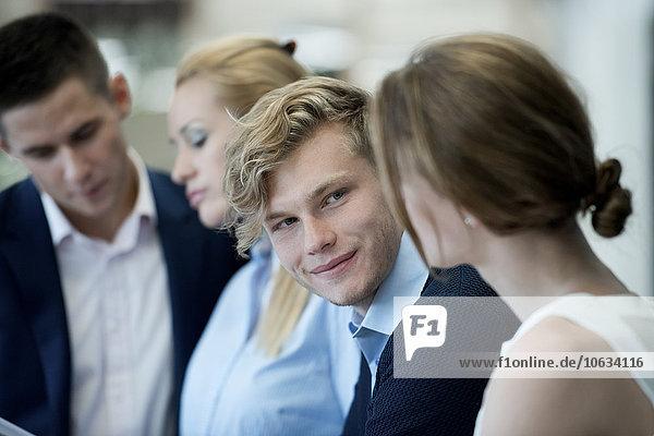 Lächelnder Geschäftsmann mit Blick auf die Kollegin