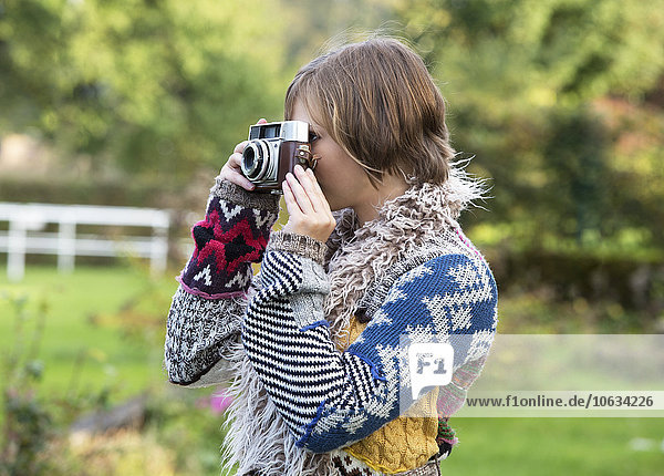 Junge Frau beim Fotografieren mit einer alten Kamera in der Natur