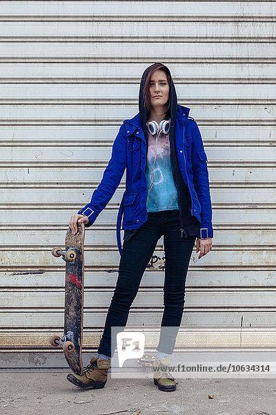 Portrait einer jungen Frau mit Skateboard