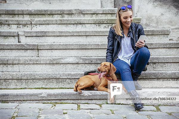 Lächelnde Frau mit Smartphone sitzend neben ihrem Hund auf der Treppe Lächelnde Frau mit Smartphone sitzend neben ihrem Hund auf der Treppe