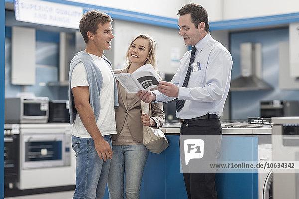 Verkäuferin im Gespräch mit dem jungen Paar Einkaufsküchenausstattung