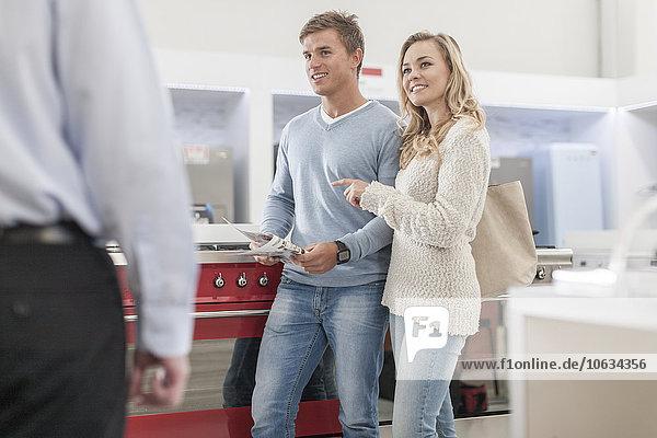 Junges Ehepaar beim Einkaufen Küchenausrüstung auf der Suche nach einer Verkäuferin