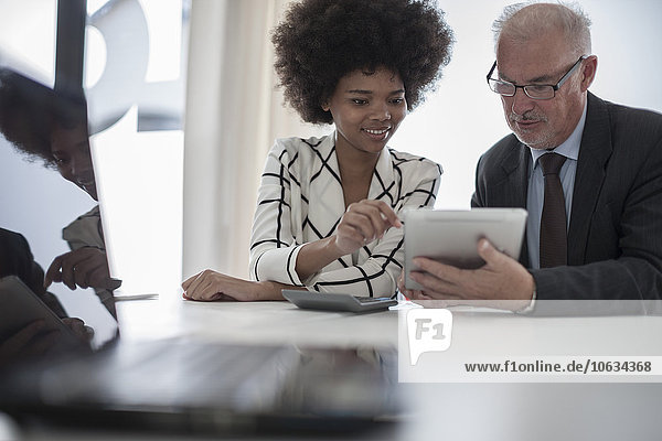 Geschäftsmann und Frau mit digitalem Tablett und Taschenrechner