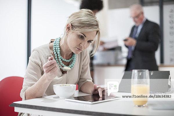 Frau beim Frühstücken im Büro