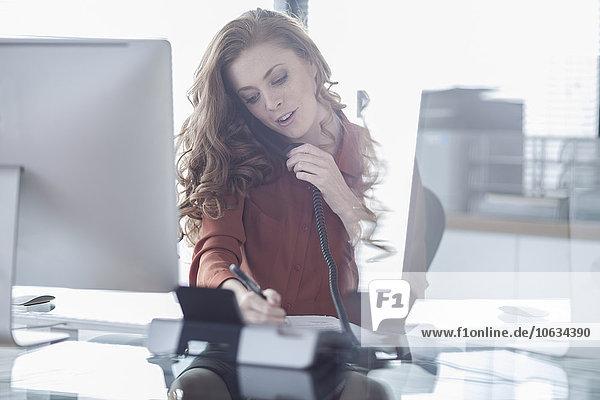 Junge Frau am Telefon am Schreibtisch