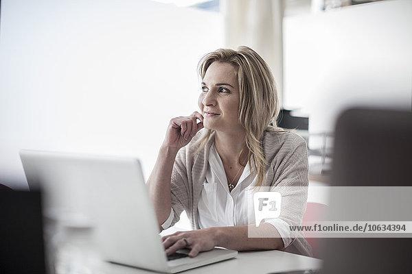 Lächelnde Geschäftsfrau am Schreibtisch mit Laptop