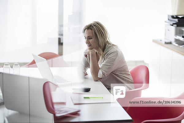 Lächelnde Geschäftsfrau im Konferenzraum mit Laptop