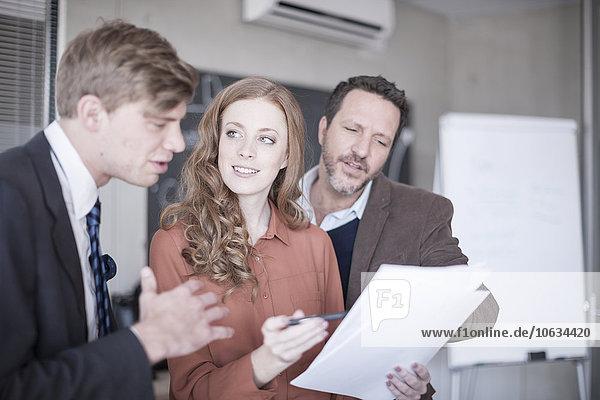 Drei Kollegen im Büro diskutieren über Papiere