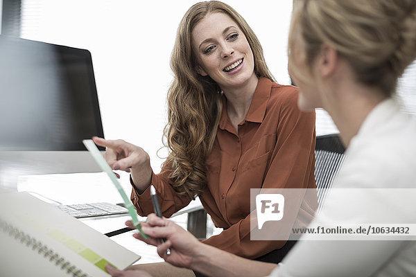 Zwei Kollegen im Büro im Gespräch am Schreibtisch