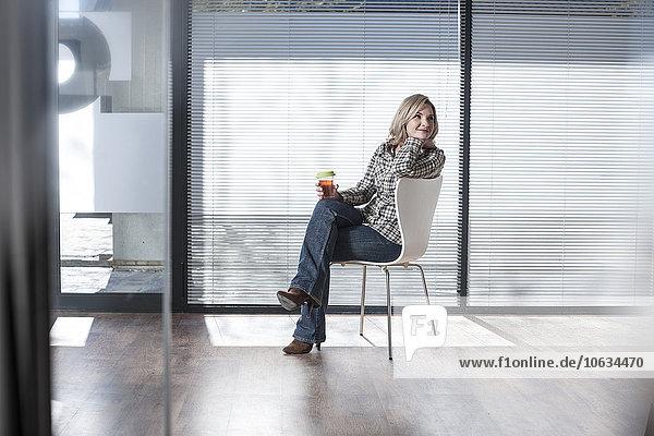 Frau auf einem Stuhl im Büro sitzend  denkend