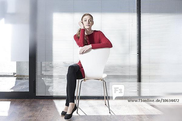 Frau auf einem Stuhl im Büro sitzend