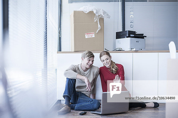 Zwei Kollegen sitzen auf der Büroetage mit Laptop