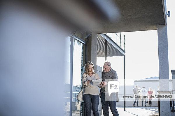 Zwei Kollegen vor dem Bürogebäude diskutieren über Papier