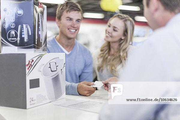 Junges Paar am Ladentisch beim Einkaufen