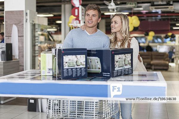 Junges Paar mit Kauf am Stehtisch