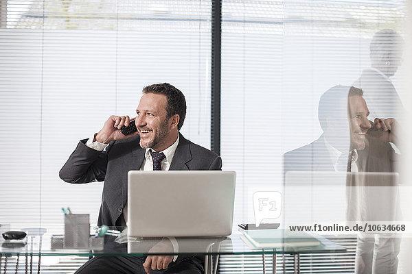 Lächelnder Geschäftsmann am Schreibtisch mit Laptop und Telefon