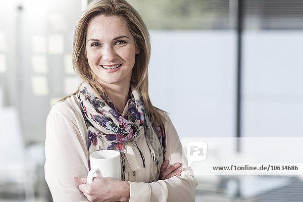 Porträt einer lächelnden Frau mit Kaffeetasse im Büro