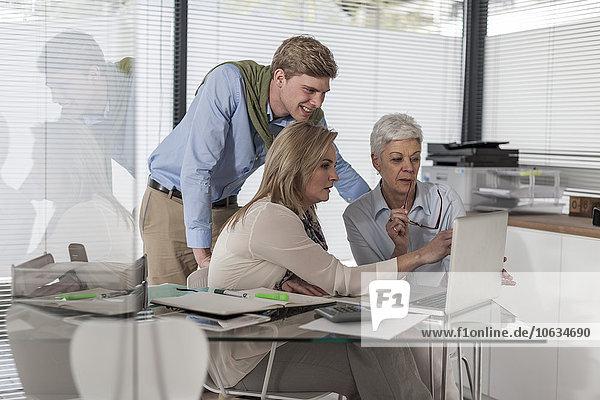 Drei Kollegen im Büro arbeiten am Laptop