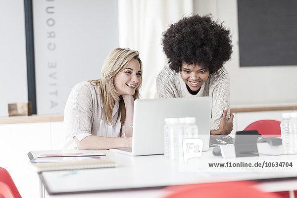 Zwei Kollegen im Büro arbeiten gemeinsam am Laptop